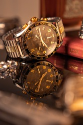 silver and gold watch sitting on a reflective table