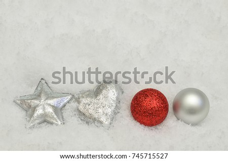 silver and red Christmas tree ball ornaments with silver heart and star on snow background, close up  / Red and Silver Christmas decoration on Snow    #745715527