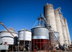 Silver and white storage silos, Agricultural industrial containers against a deep blue sky in Australia.