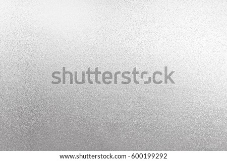 Silver background foil texture shiny light metal paper. White gold glitter shimmer dark wall bright card.