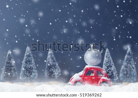 Stock Photo Silver ball christmas on red car toy with blurred tree background and snow. Christmas holiday celebration and new year 2017 background concept, copy space, filter effect.