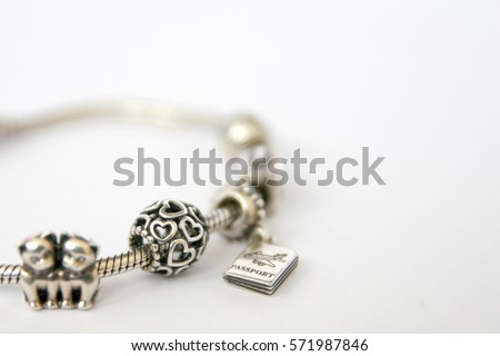 Silver beads and charms bracelets isolated on white background. Heart charms, globe, kitties, journey, passport and suitcase. Photo of Macro shot of jewelry silver charms.