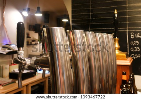 Silver beer taps with black handles and beautiful reflections in a craft beer bar with a black board with empy space during evening