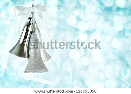 Silver bells hanging against an abstract background of icy blue holiday lights. - stock photo
