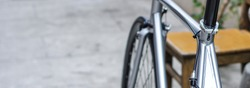 Silver bicycle frame fixed gear bike with brake on concrete floor rear view