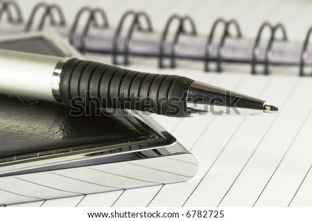 Silver-black pen lying on opened  notebook