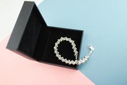 Silver bracelet in black gift box on blue, pink background.