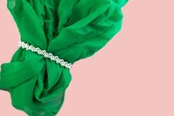 Silver bracelet in green scarf on pink background.