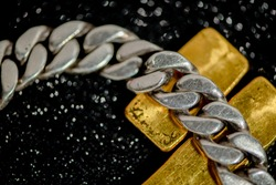 Silver bracelet placed on a gold bar on a black bokeh background