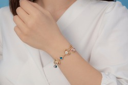 Silver bracelet with chain attached on women's wrist with white clothes and nail polish