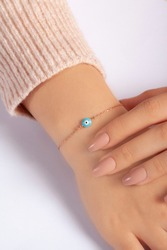 Silver bracelet with evil eye bead on the wrist of the lady in a well-groomed pink sweater