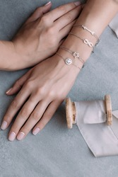 silver bracelets on a female hand on a gray background. on bracelets, decor in the form of arrows, infinity, star and smile. next to it is a silk ribbon reel