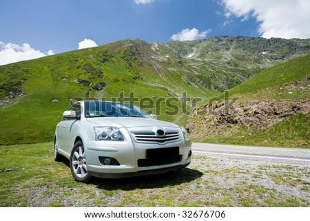 Silver car near a road through mountains