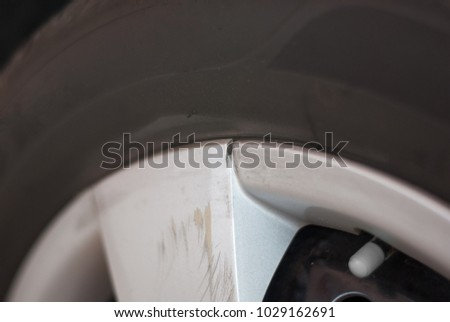 Stock Photo Silver car tire rim is broken and scratched because of hitting something, cracked, needed to replace the new one