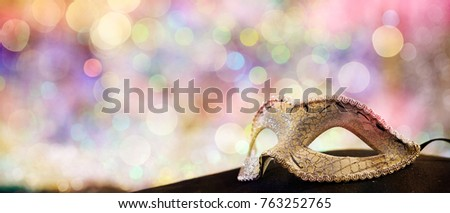 Silver carnival mask on black surface, colorful bokeh background