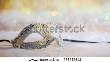 Silver carnival mask on white surface, abstract bokeh background