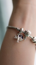 silver Charm bracelet close up  with cute boy travel charm