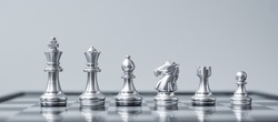 Silver Chess figure team (King, Queen, Bishop, Knight, Rook and Pawn) on Chessboard against opponent during battle. Strategy, Success, management, business planning, tactic, politic and leader concept