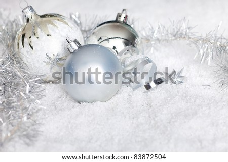 silver christmas ball ornaments lying in snow, space for your text