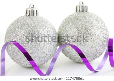 Silver Christmas baubles on white with a purple  ribbon