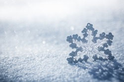 Silver Christmas decoration. Beautiful snowflake on real snow outdoors. Winter holidays concept