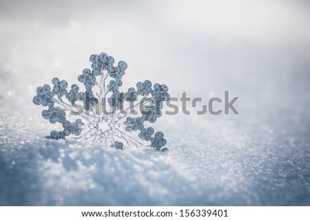 Silver Christmas decoration Beautiful snowflake on real snow outdoors Winter holidays concept