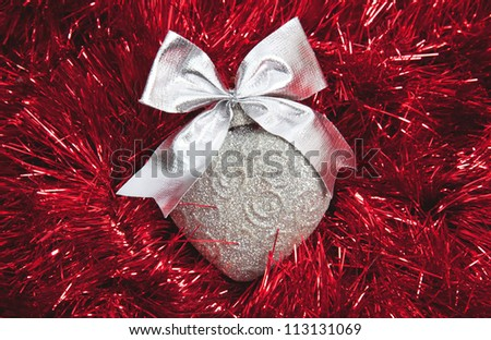 Silver Christmas heart on red tinsel background