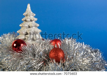 Silver christmas tree and red globes on blue background