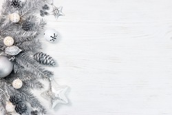 silver christmas tree branches decorated with toys, cones and garland lights on white wooden desk. holiday background.