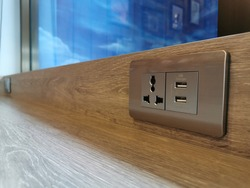 Silver color electrical wall socket adapter, Three-plug power outlet and two universal USB charger socket on the wooden table in the coffee shop.