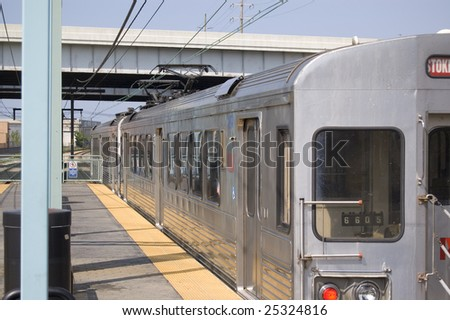 Silver commuter train at station.