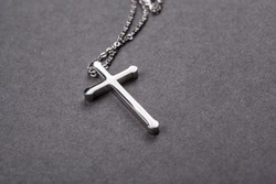 Silver cross on a gray background close up image
