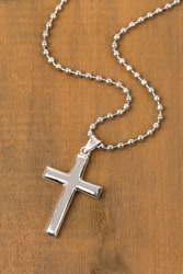 Silver cross with necklace on wooden background
