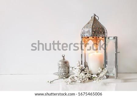 Silver  decorative cup of tea, white flowers, prunus tree blossoms and glowing Moroccan lantern on table background. Iftar dinner. Ramadan Kareem greeting card, invitation. Eid ul Fitr muslim holiday.