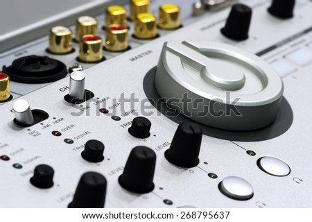 Silver DJ mixer controller with buttons, switches, faders, knobs, other toggle items, plugs and connectors, selective focus