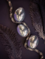 Silver eggs with feather and beaded silver necklace on a dark background, Easter