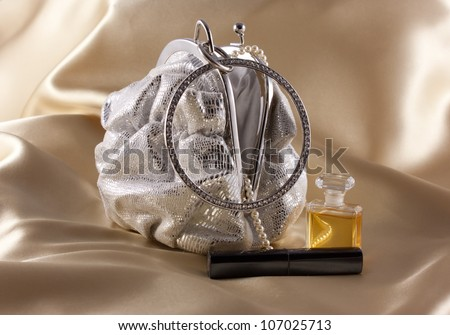 Silver evening bag with pearls, lipstick and perfume against a gold background