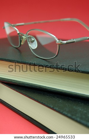 Silver eyeglasses on top of two books on red background