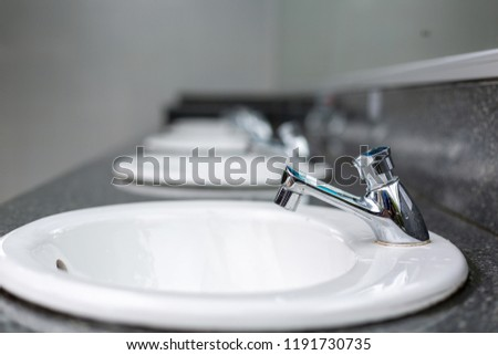 Silver faucet in bathroom,flow of water from faucet #1191730735