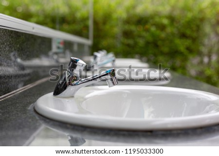 Silver faucet in bathroom,flow of water from faucet #1195033300