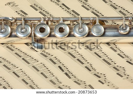 Silver flute instrument resting on an old faded music score
