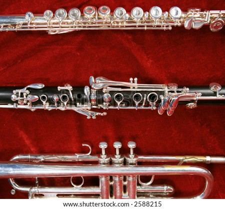 Silver flute,trumpet and clarinet on red velvet background