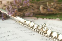 Silver Flute, woodwind brass instrument in classical orchestra. Silver modern flute on white sheet music score note for education and performance. Song composer on paper with instrument.