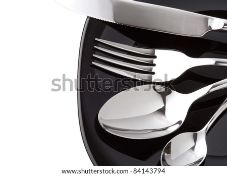 silver fork, knife and spoon as utensils on plate isolated at white background