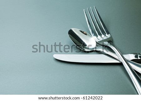 Silver fork, knife and spoon  over grey background.
