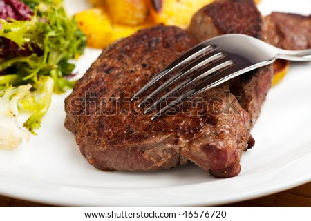 silver fork on a steak with salad and potatoes