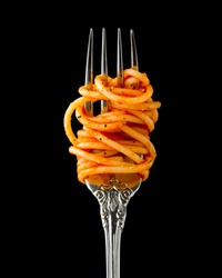 Silver fork wrapped in spaghetti with tomato sauce