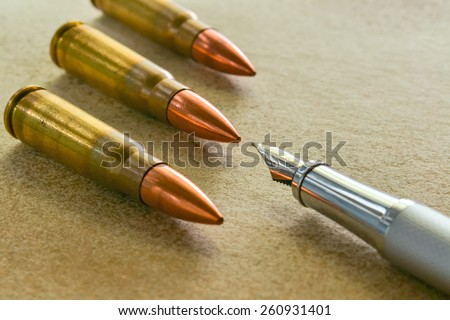 Photo of Silver fountain pen and three bullets arranged in the corners of the image