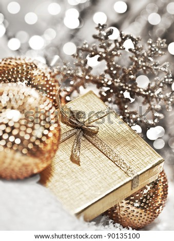Silver gift box with baubles decorations, Christmas tree ornament for winter holidays, present with abstract bokeh shiny glowing blur lights background