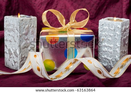 Silver gift box with silver candles and ribbons on burgundy background